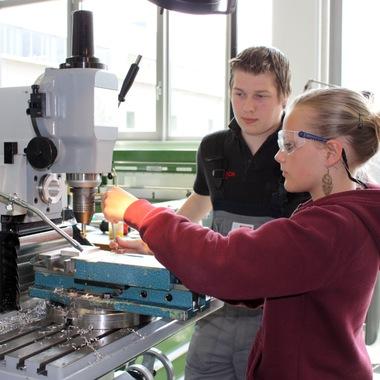 Bosch-Lehrlinge unterstützen Mädchen, die im Zuge des Girls´ Days ins Bosch-Werk Hallein gekommen sind, beim Fertigen eines Briefbeschwerers an einer Fräsmaschine.