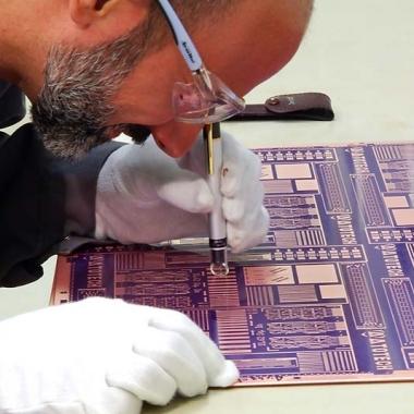 Atotech Deutschland GmbH: Atotech-Mitarbeiter begutachtet Leiterplatte nach Kupferabscheidung mit einem Handmikroskop